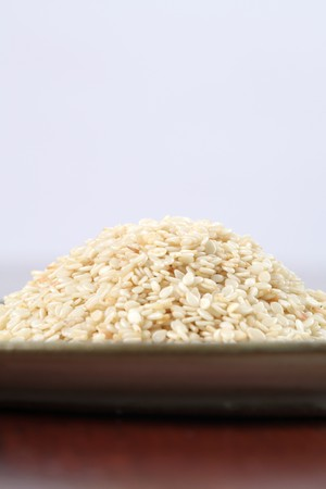 white sesame seeds: Heap of white sesame seeds on a plate Stock Photo