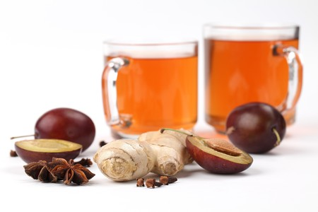 Plum tea with ginger, anise and clove on white background