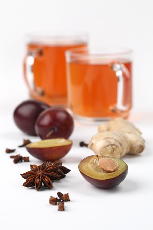 Plum tea with ginger, anise and clove on white background photo