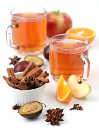 Spicy winter hot drink with oranges, apples, plums, cinnamon, anise and clove on white background