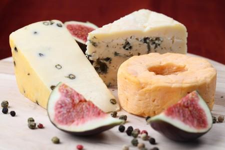 tabla de quesos: Diversos tipos de queso con higos frescos en una tabla para cortar