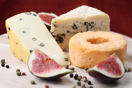 cheeseboard: Various kinds of cheese with fresh figs on a cutting board