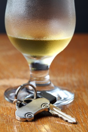 Car key with car-shaped pendant and a glass of beer photo