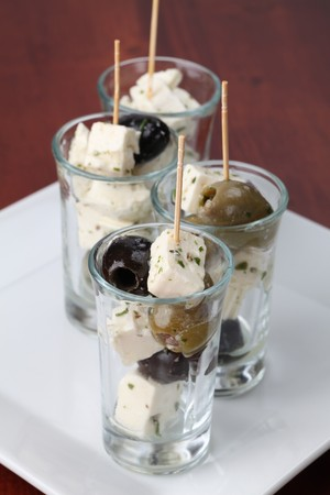Appetizers in small glasses with black and green olives and feta cheese photo