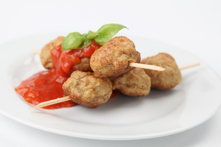 Roast meatballs on skewers with tomato sauce. Shallow DOF photo