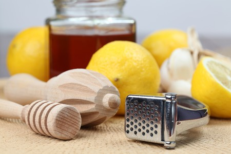cold remedy: Honey dipper, juicer and garlic press with honey, lemons and garlic as natural medicine. Focus on foreground.  Stock Photo