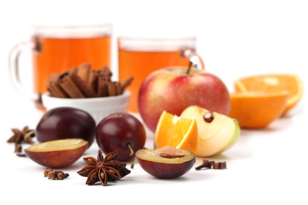 Spicy winter hot drink with oranges, apples, plums, cinnamon, anise and clove isolated on white background photo