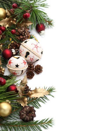 Christmas border with jingle bells and other Christmas ornaments and decorations isolated on white. Shallow dof Standard-Bild