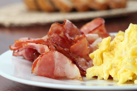 Scrambled eggs and slices of bacon on a plate Standard-Bild