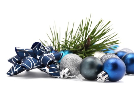 blue christmas background: Fancy bow with blue and silver Christmas ornaments and a pine twig isolated on white background. Shallow dof Stock Photo