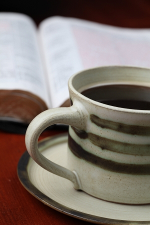 Morning coffee with the Bible in background. Shallow dof