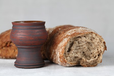 Chalice with red wine and bread in background. Shallow dof, copy space