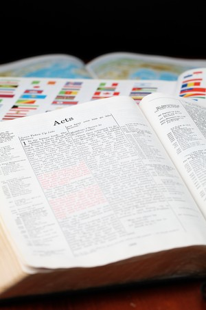 Bible open to the Book of Acts (the book that describes spreading the Gospel to the World) and a world map in the background. World missions concept. photo