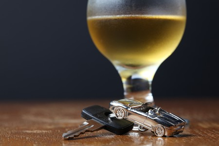 drink and drive: Car key with car-shaped pendant and a glass of beer