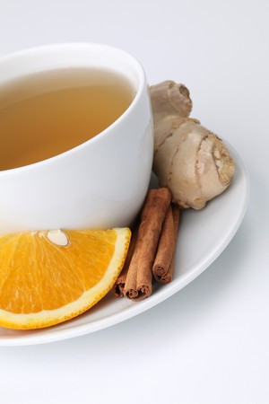 ingefära: Cup of orange tea with cinnamon and ginger on white background. Shallow dof