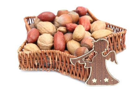 Christmas angel with basket in the shape of star with hazelnuts, walnuts, almonds and pecans isolated on white background. Shallow dof photo