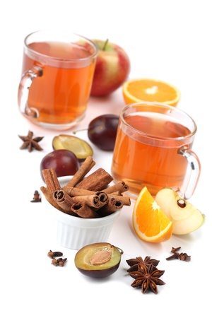 Spicy winter hot drink with oranges, apples, plums, cinnamon, anise and clove isolated on white background. Shallow dof photo