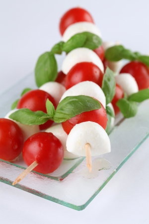 Cherry tomatoes and mozzarella on skewers, garnished with basil leaves and olive oil photo