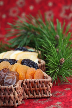 Christmas tree basket with dried fruits on red background. Shallow dof photo