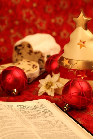 bible open to the christmas story and stollen with christmas decorations in background stock photo