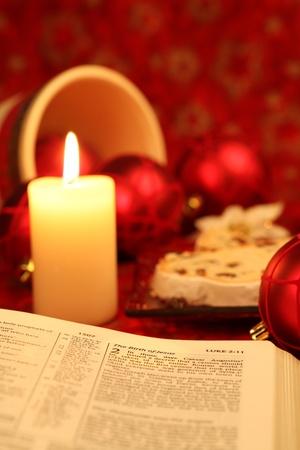 weihnachtskuchen: Bibel der Weihnachtsgeschichte und Stollen mit Weihnachtsschmuck im Hintergrund offen