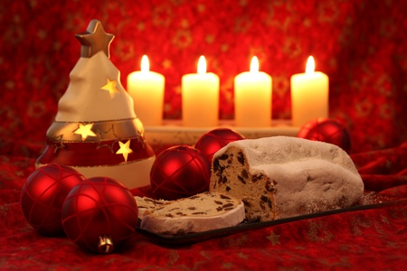 Christmas stollen with ornaments and candles on red background Stock Photo - 8384983