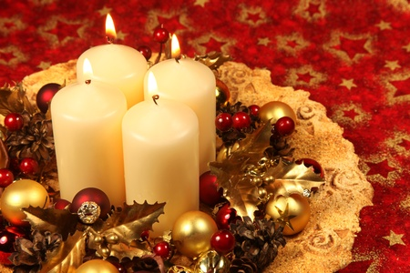 Christmas decoration with four candles on red Christmas background. Shallow DOF, copy space photo