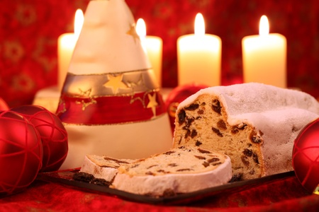 Christmas stollen with ornaments and candles on red background Stock Photo - 8455528