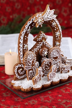 Gingerbread nativity scene and the open Bible on red Christmas background photo