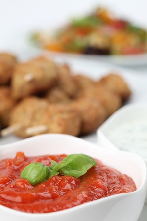 Tomato dip and roast meatballs in background photo