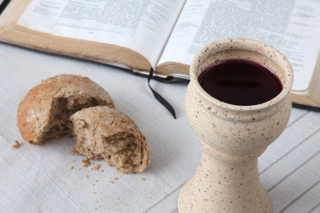 Chalice with red wine, bread and Holy Bible on a tablecloth. Shallow dof Standard-Bild