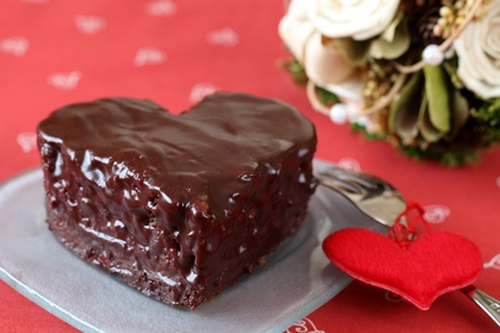 Heart shaped chocolate cake with heart decoration and bouquet