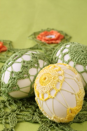 Easter eggs with beautiful yellow and green crochet decoration  photo