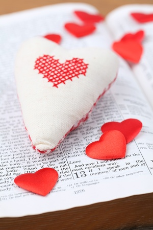 Bible open to 1st Corinthians 13, a passage about love, and heart shaped decorations. Shallow dof Stock Photo - 8601862