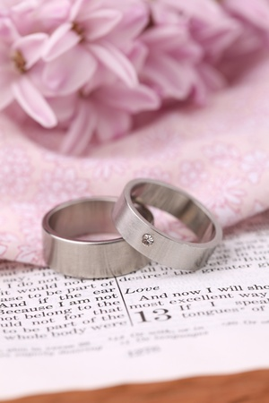 Titanium wedding rings on the Bible open to 1st Corinthians 13, a passage about love. Shallow dof photo