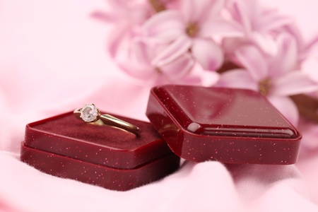 Gold engagement ring with diamond in a red box. Pink hyacinth in background. Shallow dof photo