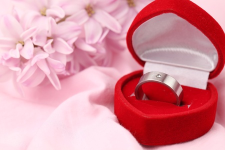 Titanium engagement ring with diamond in a heart shaped box on pink background with pink hyacinth. Shallow dof photo