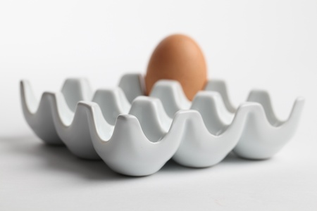 Ceramic egg holder with one brown chicken egg. Shallow dof photo