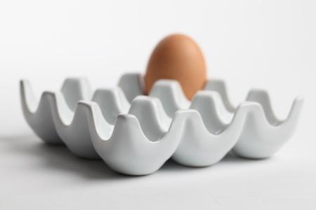 chicken egg: Ceramic egg holder with one brown chicken egg. Shallow dof