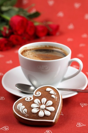 Gingerbread heart with coffee and red roses on red background. Shallow dof photo
