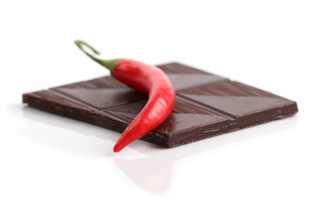 Red chili pepper and dark chocolate on white background. Shallow dof photo