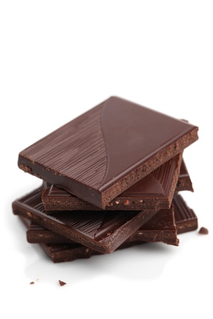 chocolate block: Stack of dark chocolate pieces on white background. Shallow dof