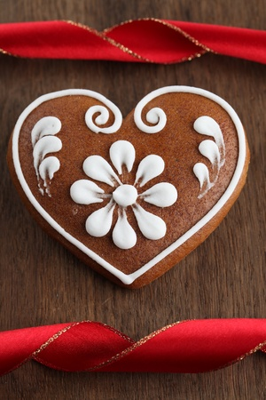 Gingerbread heart and red ribbon on brown wooden background. Shallow dof photo