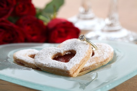 Gold engagement ring with shortbread hearts on a plate, red roses and wine glasses. Shallow dof photo