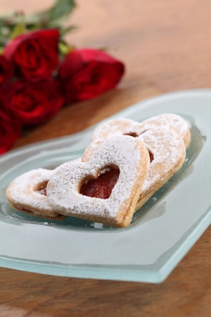 Shortbread hearts on a plate and red roses. Shallow dof photo