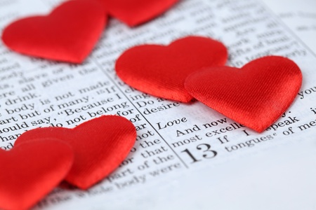 Bible open to 1st Corinthians 13, a passage about love, and little heart shaped confetti. Shallow dof photo