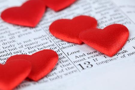 Die Bibel für 1. Korinther 13, eine Passage über die Liebe, und little Heart shaped Konfetti. Shallow dof Standard-Bild - 8771043