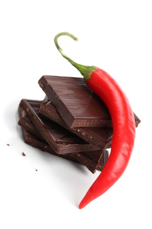 Red chili pepper on stack of dark chocolate pieces on white background. Shallow dof photo