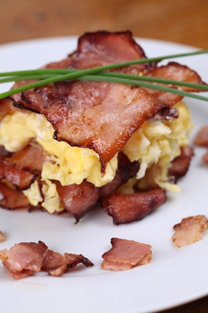 scrambled eggs: Huevos revueltos y bacon, adornado con cebollines en plato blanco