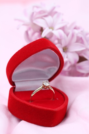 Gold engagement ring with diamond in a red heart shaped box. Pink hyacinth in background. Shallow dof photo